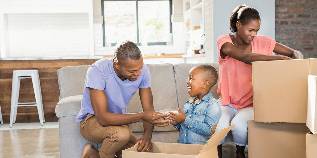 African American family packing boxes to move house
