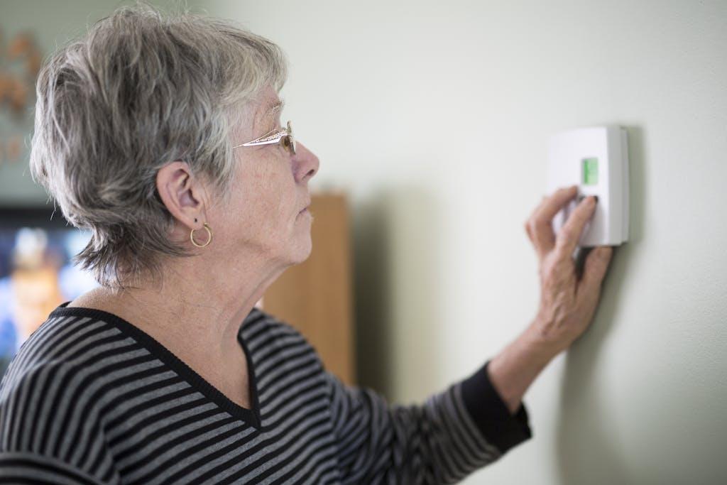 Elderly woman adjusting thermostat