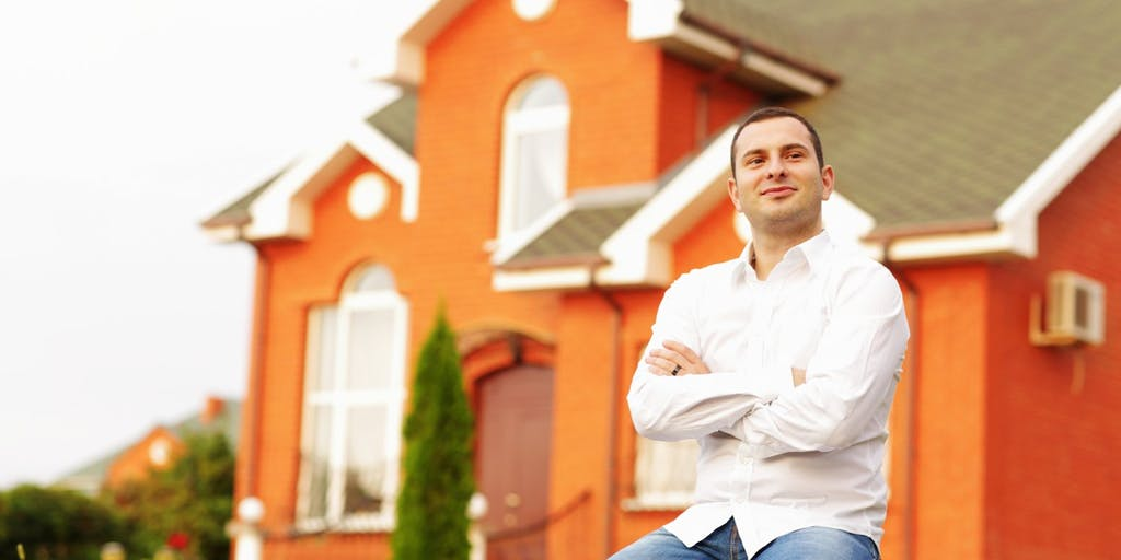 Satisfied man outside house