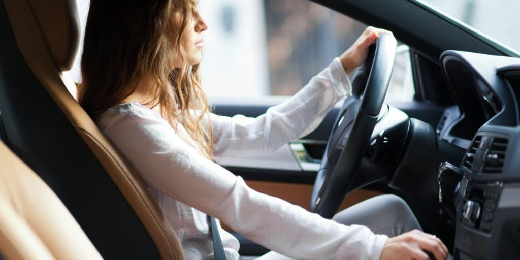 Woman driving a car with one hand on the wheel and the other on the gear stick.