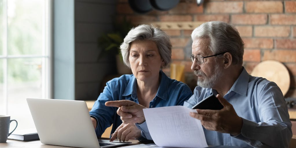Senior husband and wife sit at table at home look at laptop screen