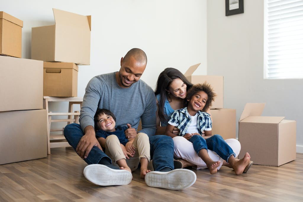 black family surrounded by moving boxes enjoying time together in new home