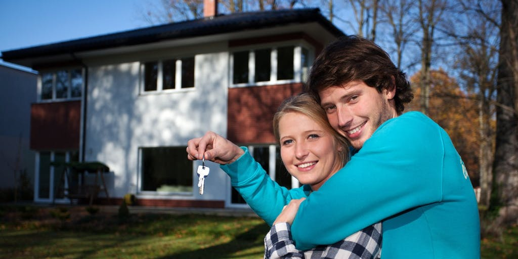 Happy couple in new home holding keys