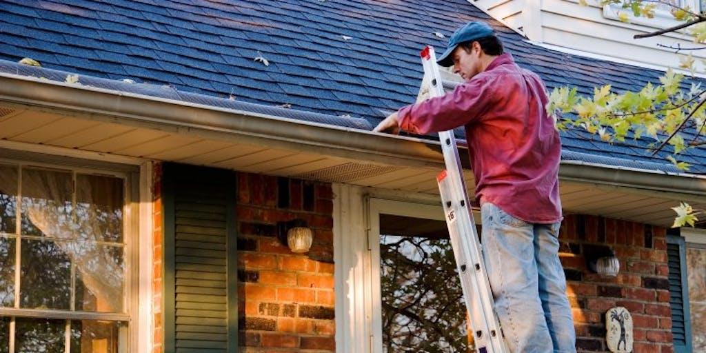 Man on ladder cleaning gutter