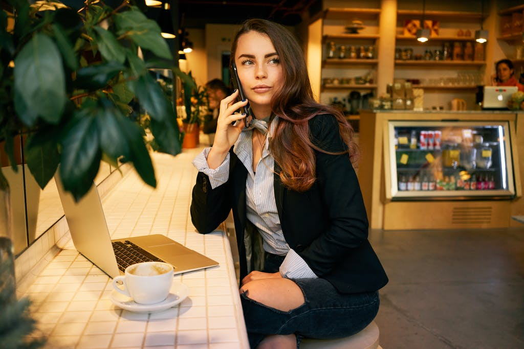 Woman using WiFi hotspot in cafe