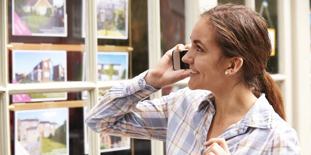 Women looking at house prices in estate agent window