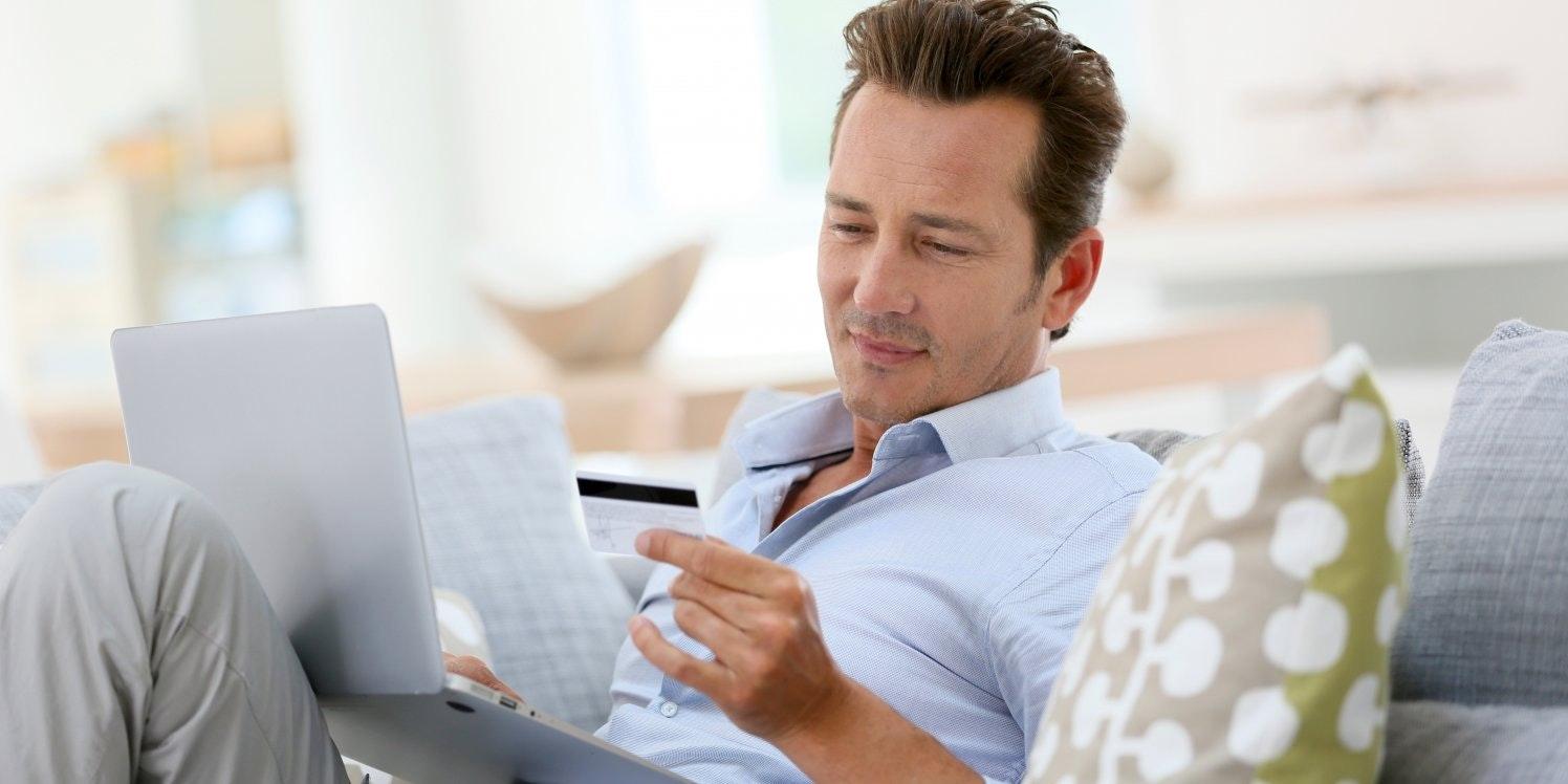 Man on sofa looking at a credit card