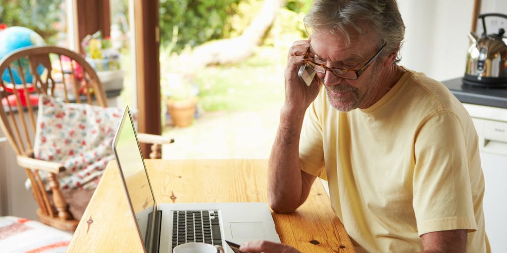 older-man-on-phone-looking-at-credit-card
