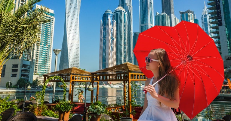 girl in city holding red umbrella