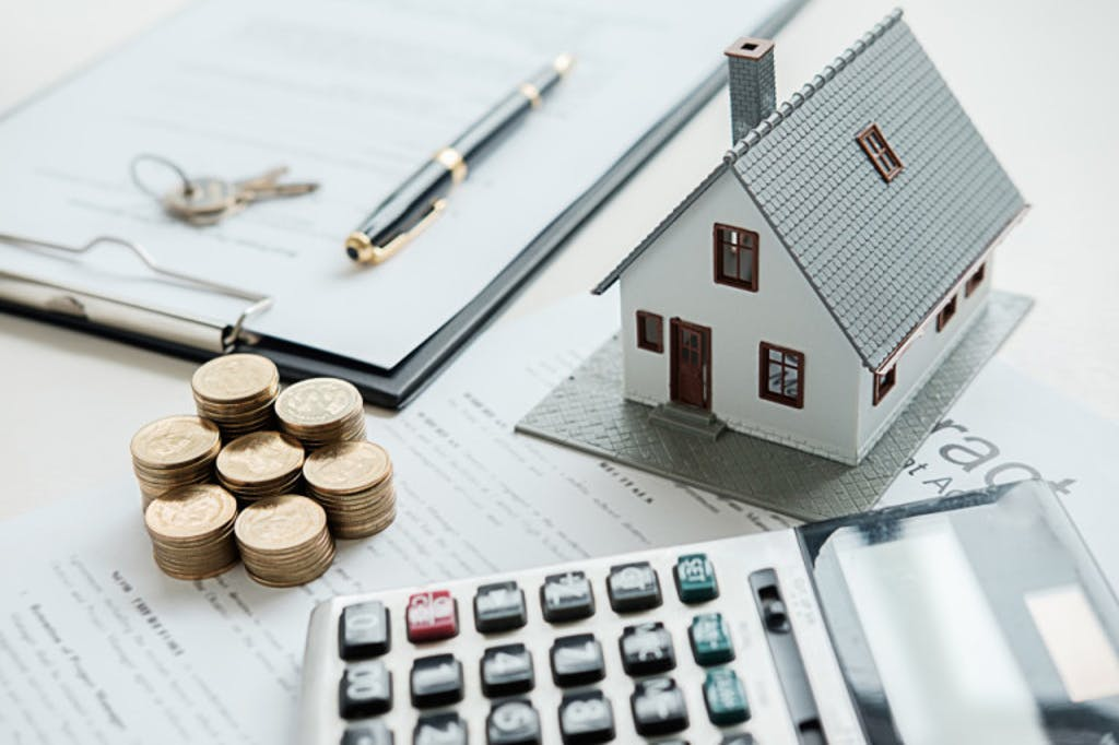 Image of model house surrounded by finances and calculator