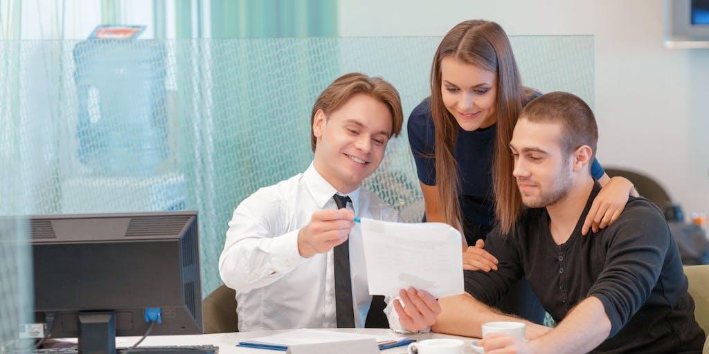 Couple talking through document with advisor
