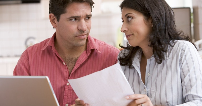 Concerned couple at home with bills and laptop