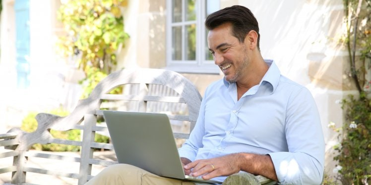 man outside working on laptop