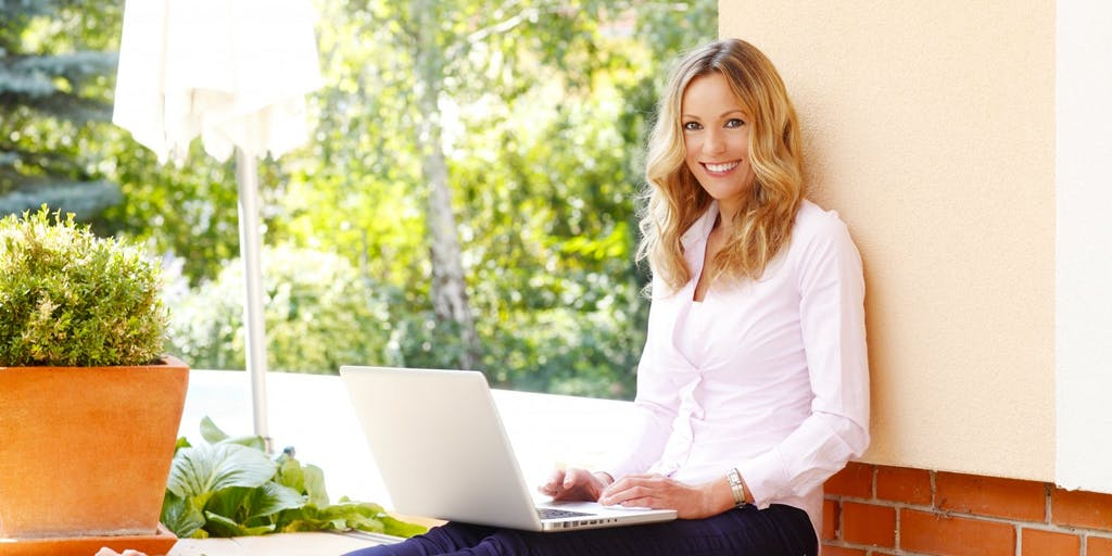 Smiling woman on laptop outdoors
